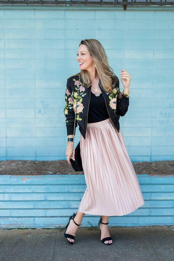 a blush pleated midi skirt, a black top, a black floral print bomber and black heeled sandals