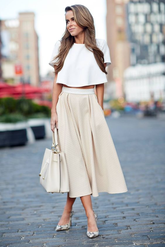 a creamy midi skirt, a white crop top with sleeves, a neutral bag and snake print shoes