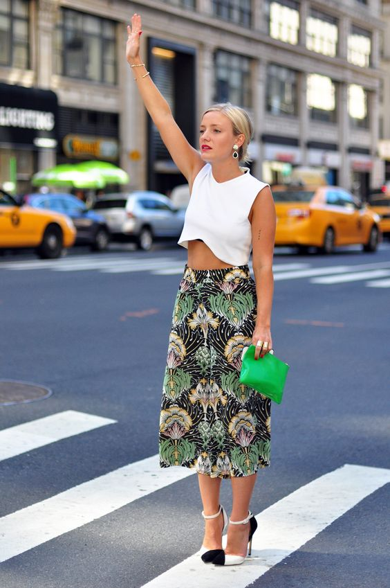 a white crop top, a printed tropical inspired midi skirt, black and white heels and a green bag
