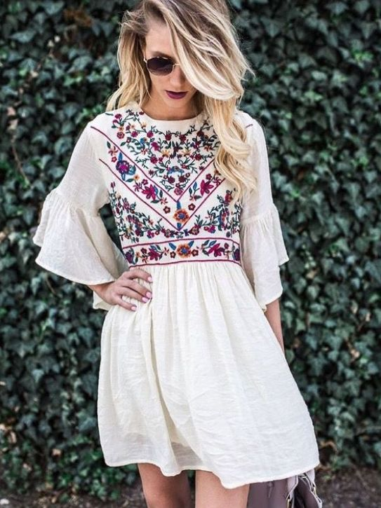 white mini dress with ruffled sleeves and colorful floral embroidery on the bodice