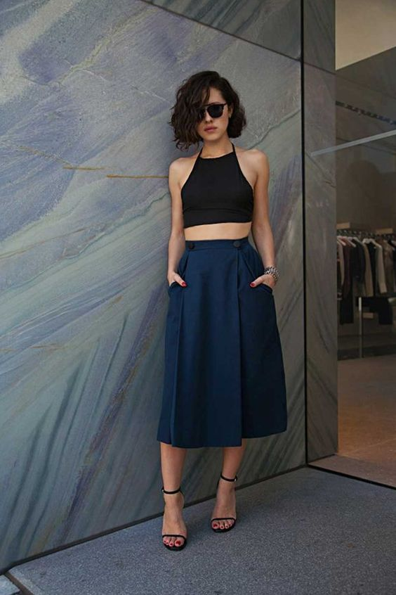 a black halter neckline crop top, a navy midi skirt with pockets and ankle strap heels