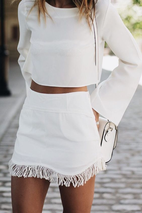 a white fringe skirt and a white crop top with long sleeves for a chic all-white summer look