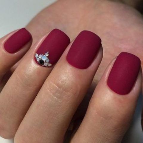matte red nails with colorful rhinestones for an accent