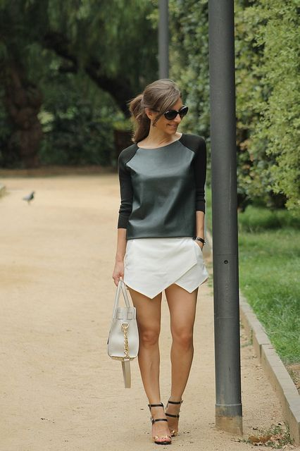 a black sweatshirt with a leather bodice and a geo white mini skirt, strappy heels