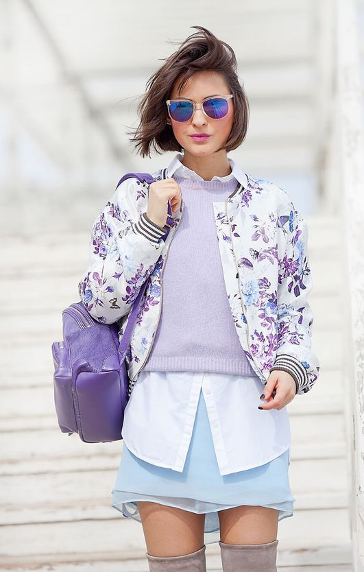 a blue mini skirt, a white shirt, a lavender sweater and a floral print bomber jacket for a pastel layered look