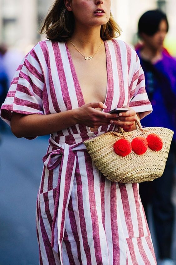 a basket bag with large red pompoms will add cheer and fun to your look
