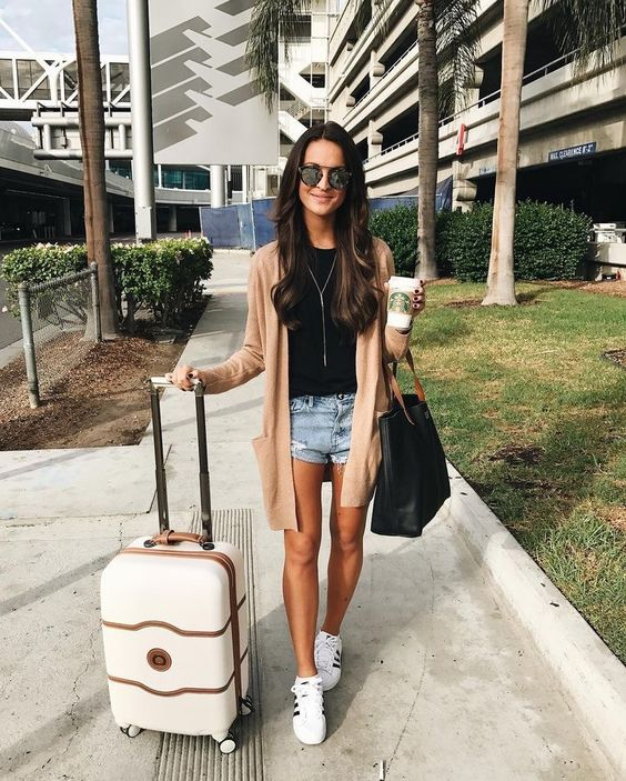 denim mini shorts, a black tee, a peach cardigan, white sneakers and a large bag - a practical and cool look