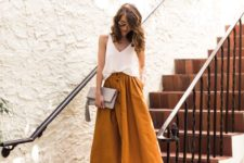 06 a mustard midi skirt with a button row, a white strap top and metallic heels