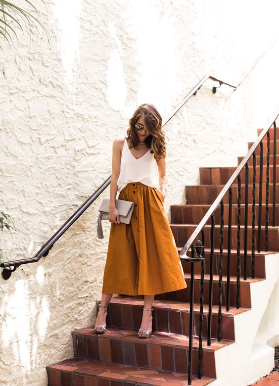 a mustard midi skirt with a button row, a white strap top and metallic heels