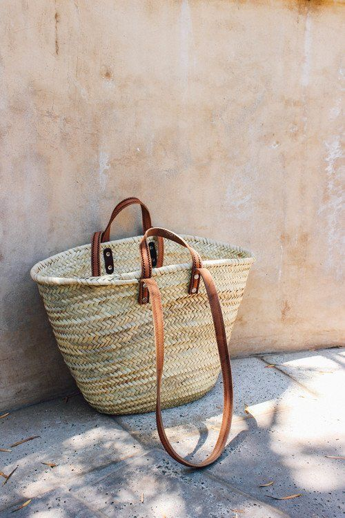 a straw tote bag with brown handles is summer and beach classics