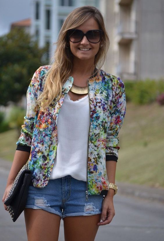 ripped denim shorts, a white top, a colroful floral print bomber jacket and a clutch