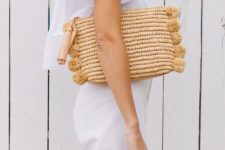 07 a straw clutch with matching pompoms is a fresh take on a traditional straw bag