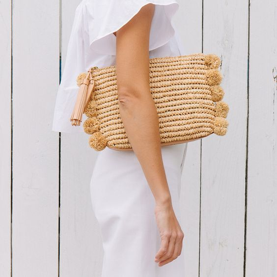 a straw clutch with matching pompoms is a fresh take on a traditional straw bag