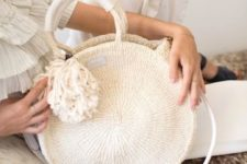 07 a white woven circle bag with a large pompom is a new version of a traditional straw bag