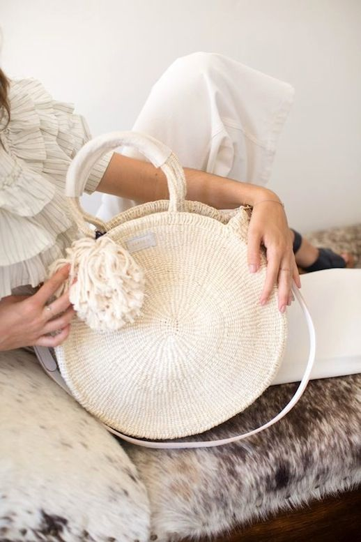 a white woven circle bag with a large pompom is a new version of a traditional straw bag