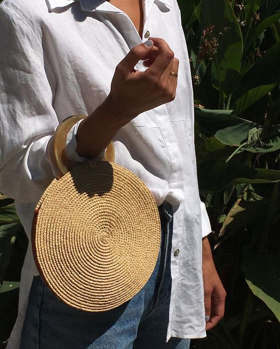 a rafia weave circle clutch with an enamel handle is a cool and eye-catchy piece