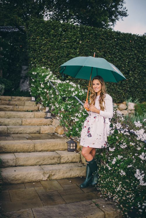 green rain boots, a floral skirt, a white long sleeve and an emerald umbrella to match