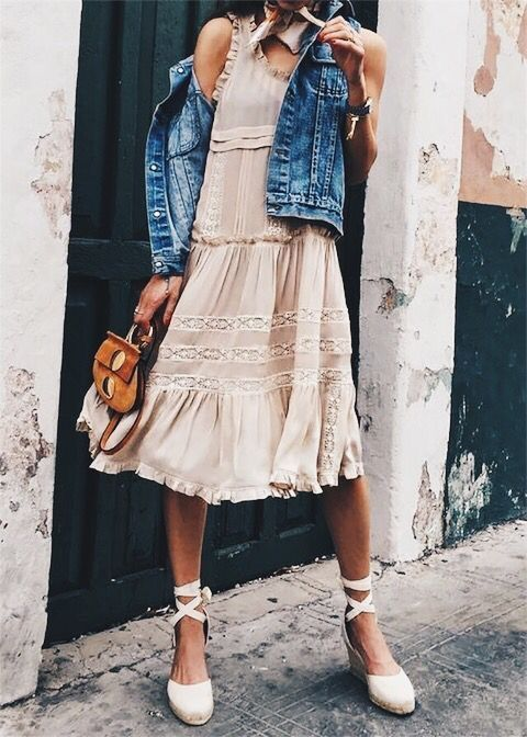 a blush knee dress with ruffles and white lace detailing with a denim vest and lace up shoes