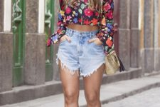 a bold floral crop top with long sleeves, high waisted denim shorts and black heels