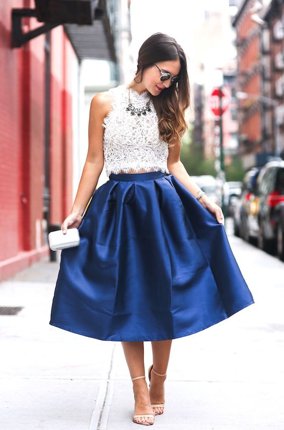 a white halter neckline lace crop top and a blue stain midi skirt, nude heels and a statement necklace