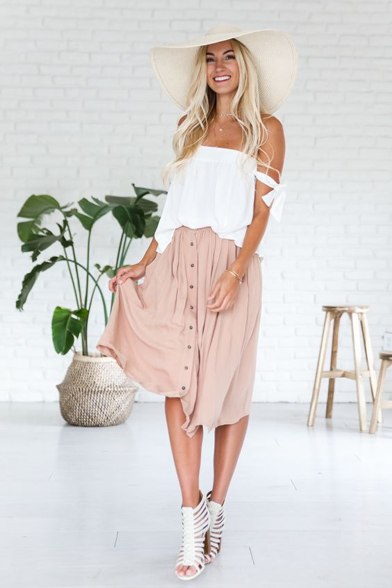 a white off the shoulder top, a blush midi skirt with a button row and strappy white heels