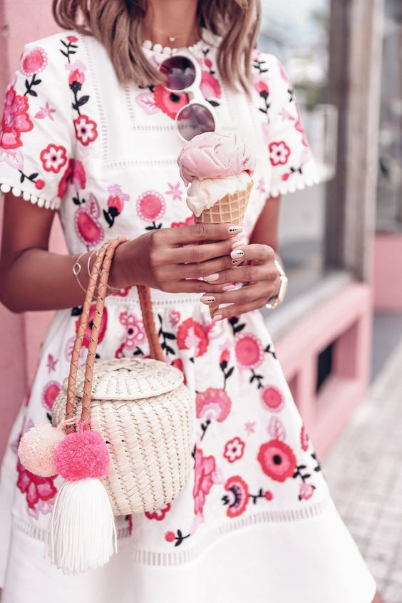 a white straw bag with a leather handle, pompoms and a unique shape