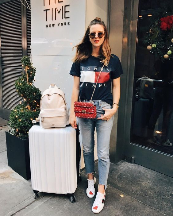 a black printed tee, distressed jeans and colorful sneakers to travel with style