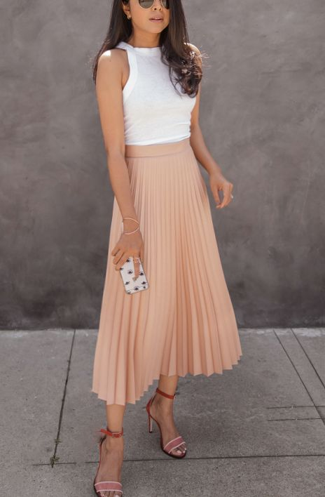 a white halter neckline top, a blush pleated midi skirt and pink shoes