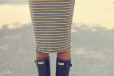 10 a white tee, a striped grey and yellow midi skirt and black rain boots