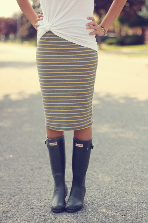 a white tee, a striped grey and yellow midi skirt and black rain boots