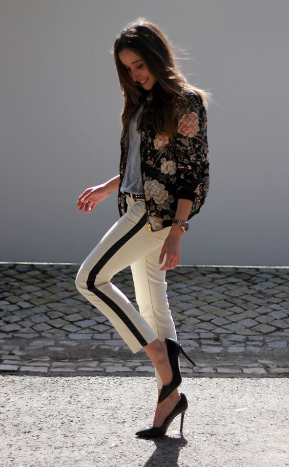 black heels, white pants with a black stripe, a grey tee and a black floral bomber jacket
