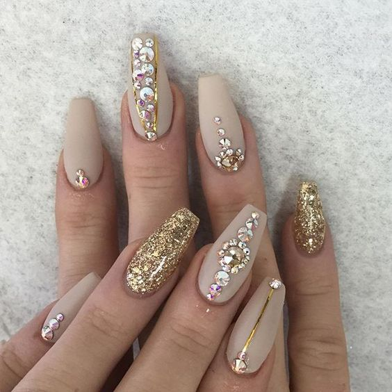 matte nude nail art with gold glitter, gold stripes and rhinestones