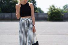 11 a black halter neckline crop top and black and white striped culottes, black heels