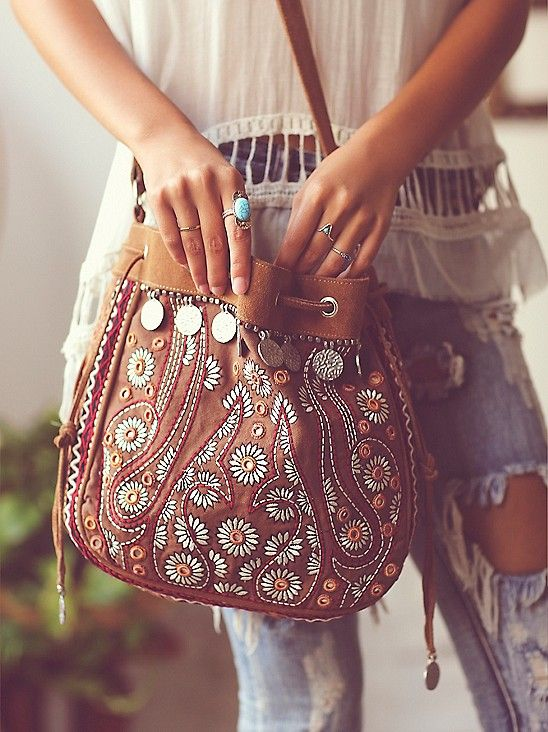 a brown leather boho bag decorated with beads, embroidery and coins
