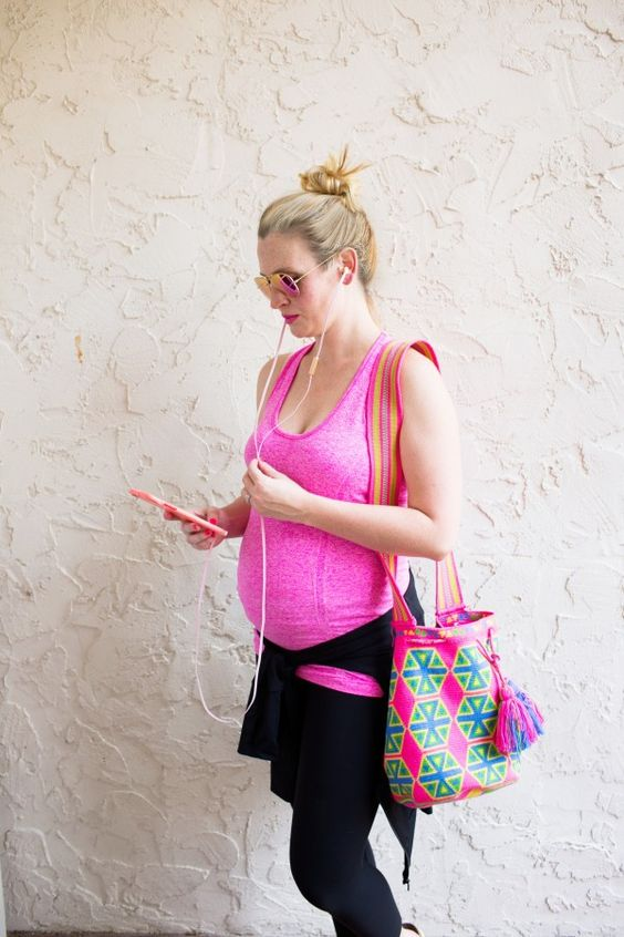 a textural pink strappy top, black leggings and a colorful printed bag