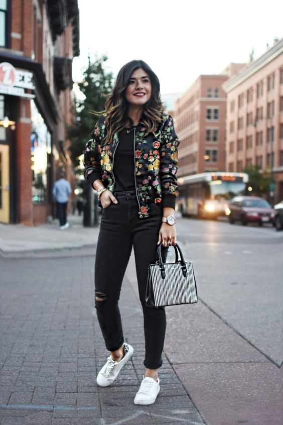 black ripped jeans, a black tee, a black floral print bomber jacket and white sneakers