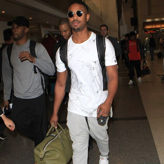 grey pants, a white printed tee, white sneakers and a black backpack