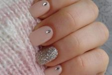 11 pink nails with a silver glitter accent one and some rhinestones