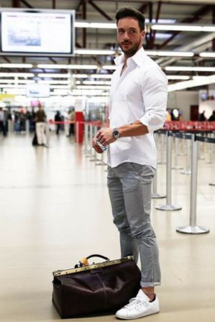 grey pants, a white shirt, white sneakers and a dark leather bag