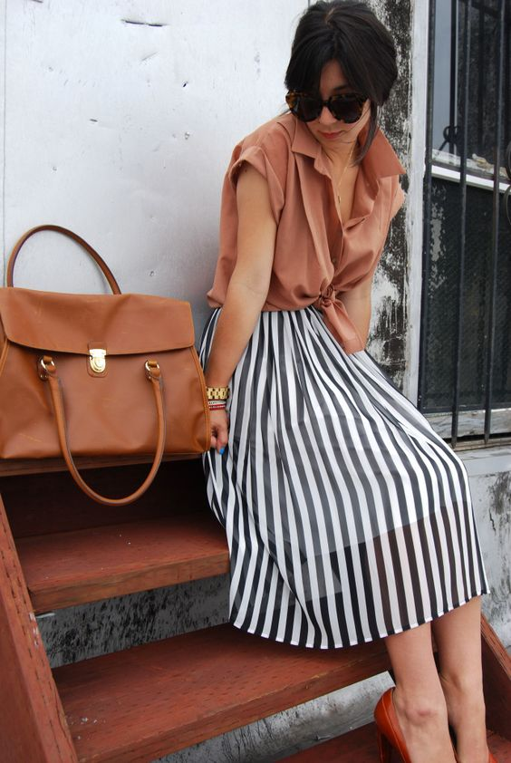a burnt orange shirt with short sleeves, a black and white striped midi skirt and brown heels