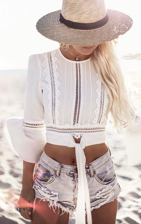 distressed denim mini shorts and a white boho lace crop top with ties and bell sleeves