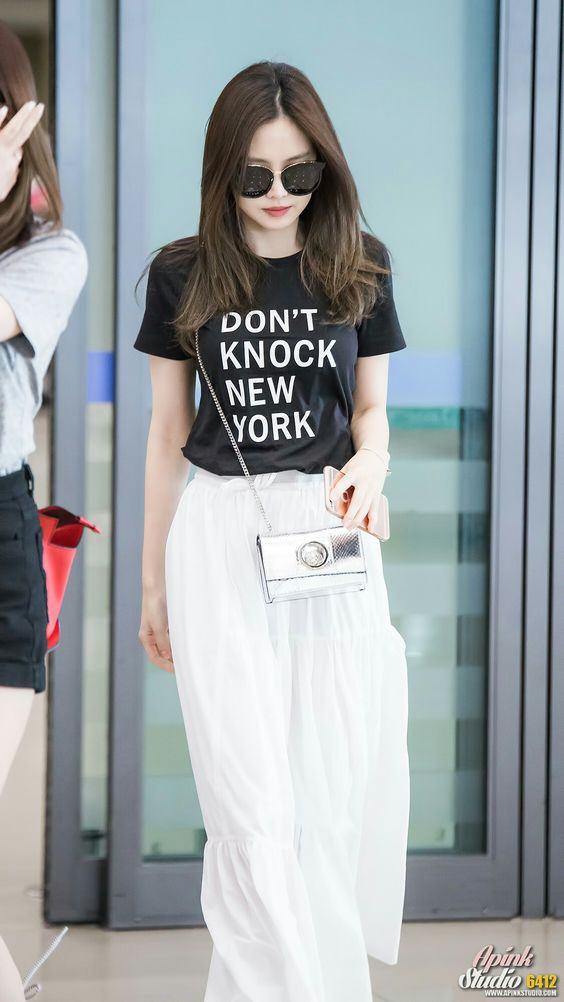 a white maxi skirt, a printed black tee and a silver crossbody for a chic airport look