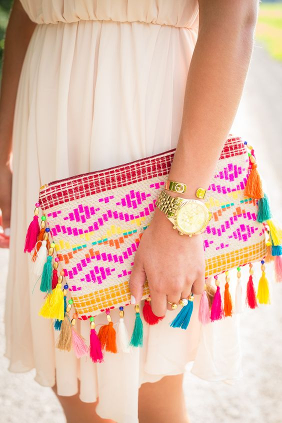 an embroidered bold clutch with bold tassels is ideal for a summer outfit