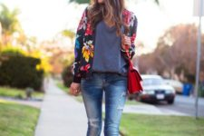 15 ripped jeans, black heels, an oversized grey tee, a black floral print jacket and a red bag