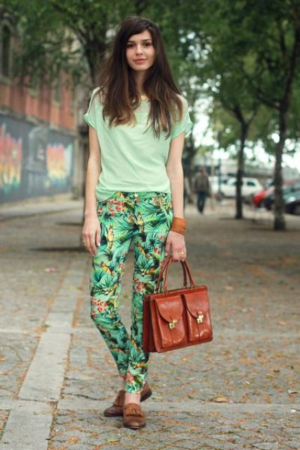 tropical print pants, a light gree tee, brown moccasins and a brown bag