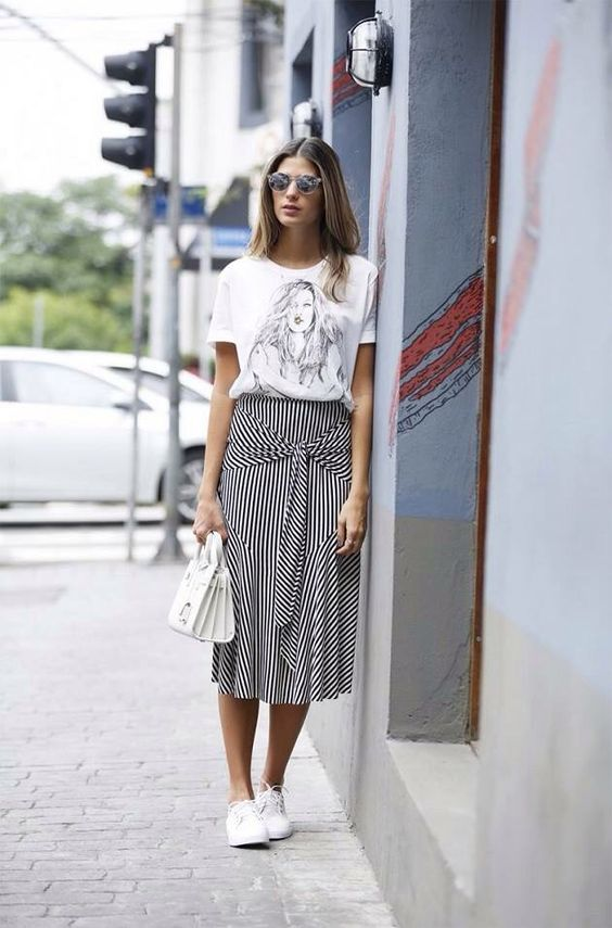 a printed white tee, a striped black and white midi, white sneakers and a white bag
