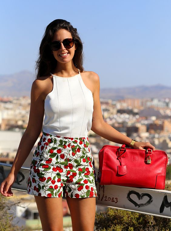 a white halter neckline sleeveless top, cherry printed high waisted shorts and a red bag for holidays