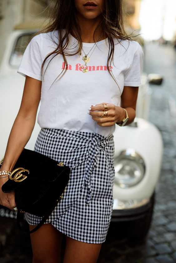 a white printed tee, a black and white gingham wrap mini and a clutch