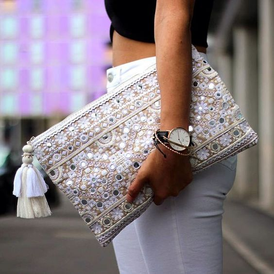 neutral-colored embroidered clutch with sequins and beads and a tassel