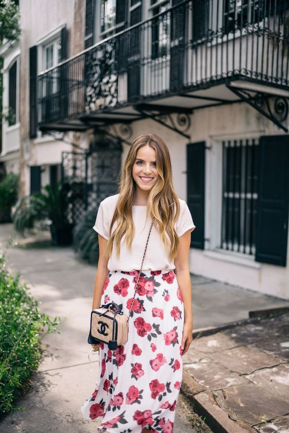a white top and a white midi skirt with a pink floral print, a pink crossbody bag